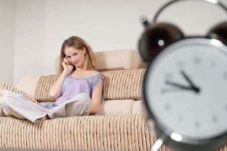 Young woman is sitting on sofa and talking via mobile phone for hours photo