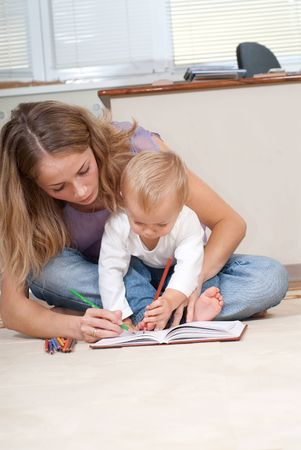 Young mother is drawing with her son photo