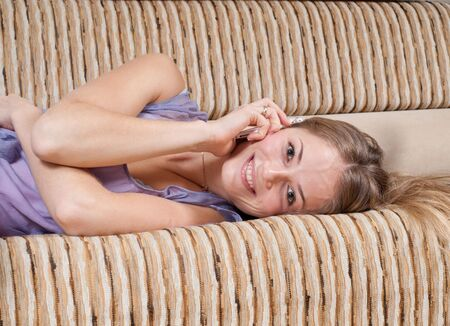 Young girl is lying on sofa and talking via mobile phone Stock Photo - 5835410