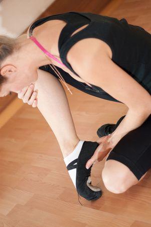 Injured ballerina in black pointes on parquet photo