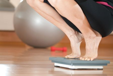 Young woman is weighting oneself in fitness gym Stock Photo - 5918413