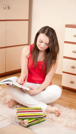 Beautiful young woman is studying on floor photo