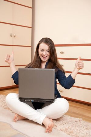 Pretty young student with laptop at home photo