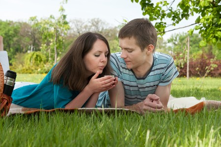 Young couple is lying in grass with cup of tea photo