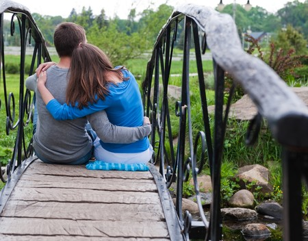 Happy couple is sitting and embracing on bridge Stock Photo - 7036117