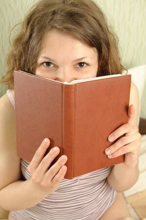 Young girl is hiding over a book in her bedroom photo