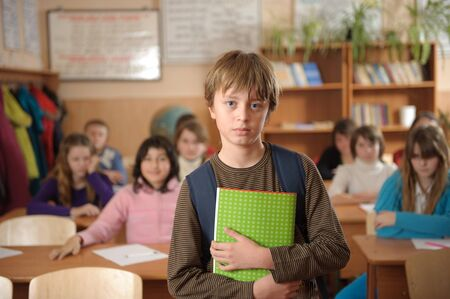 studious: Serious schoolboy is standing in front of class