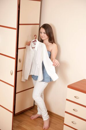 Young lady is trying on white shirt near wardrobe photo