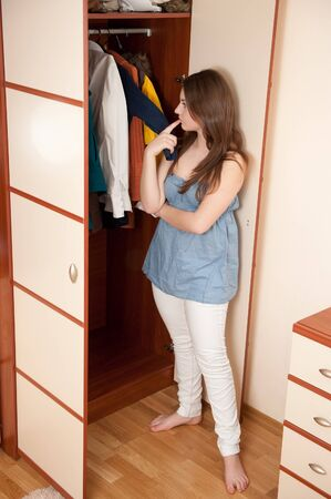 Young girl is making choice near wardrobe photo