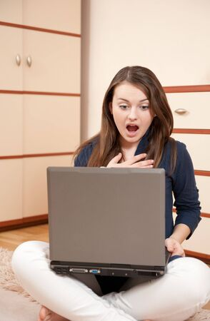 Young female is surprised during her studying with laptop photo