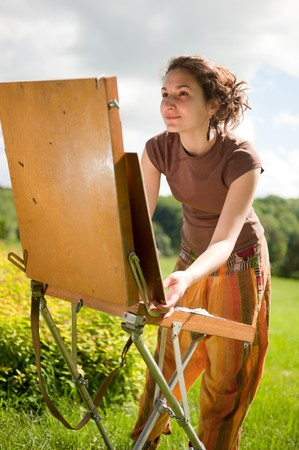 'face painting': Pretty woman is painting. Open air session. Stock Photo