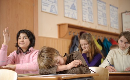 Tired boy is sleeping during school lesson photo