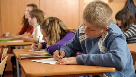 diligent: Diligent schoolboy is writing down in notebook during lesson