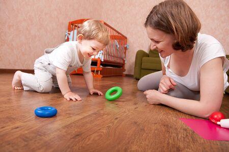 frau sitzt am boden: Junge Mutter ist mit Ihrem kleinen Sohn spielen. Lizenzfreie Bilder