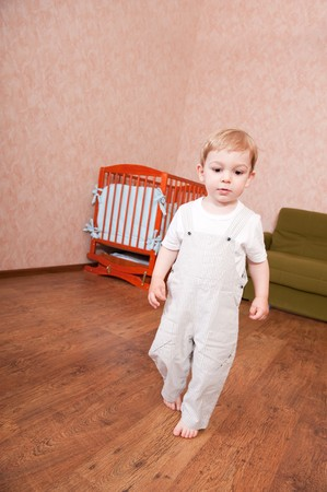Barefooted boy is walking in his bedroom photo