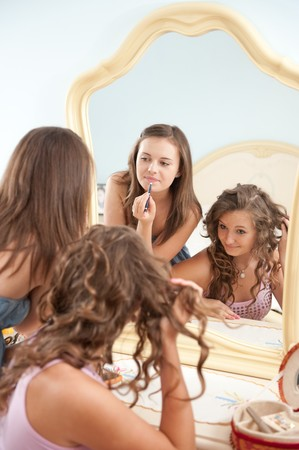 Two young girls near mirror during make-up photo