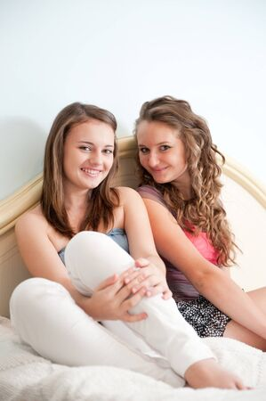 Two young girls sitting in bed and smiling photo