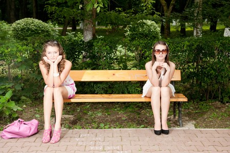 Two pretty girls arguing in park on bench Stock Photo - 8029825