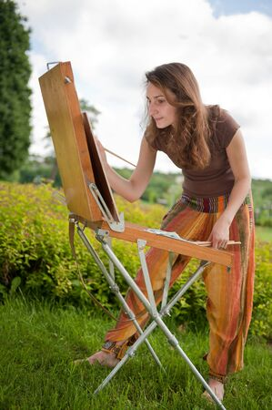 Pretty woman is painting. Open air session. Stock Photo