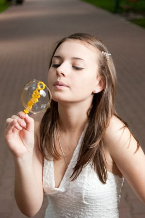 Young girl is blowing soap bubbles photo