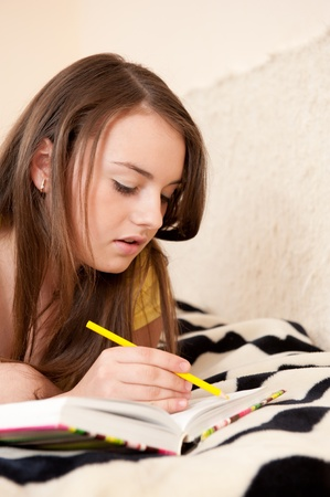 Young gilr is making notes lying down on a bed Stock Photo - 8684218