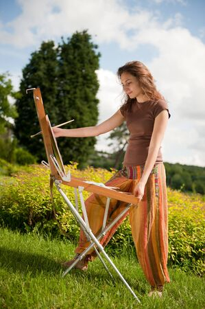Pretty woman is painting. Open air session. photo