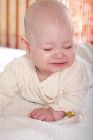 Crying baby girl lying on white towel photo