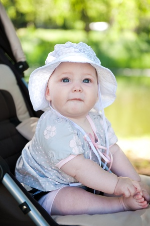 Cute baby in hat is sitting in stroller outdoors photo