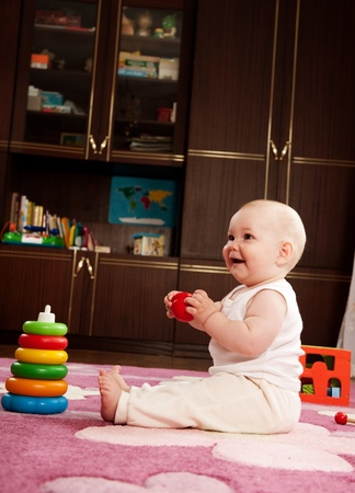 Cute baby girl s playing with toys in playroom Stock Photo - 9883924