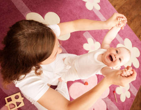 the first step: Young mother is helping her daughter to make first steps