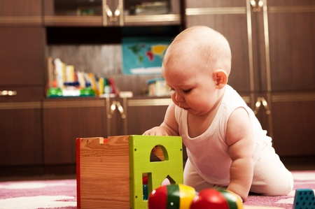 Cute baby girl s playing with toys in playroom Stock Photo - 9884000
