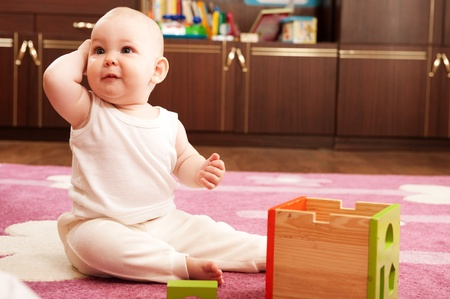 Cute baby girl s playing with toys in playroom Stock Photo - 9883978