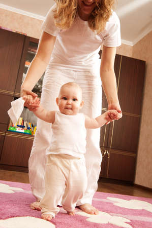 Young mother is helping her daughter to make first steps Stock Photo - 9949912
