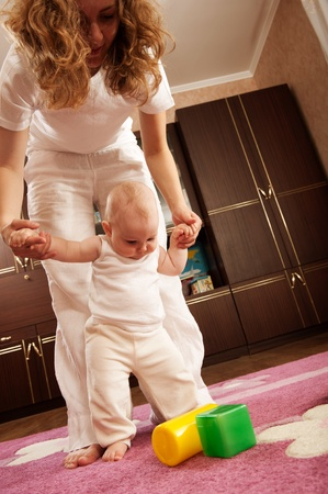 Young mother is helping her daughter to make first steps photo