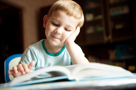 teen boy face: Little boy is reading book at home Stock Photo