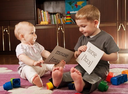 A boy aged three and a girl aged one are playing with blocks and cards with words photo
