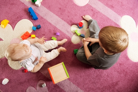 A boy aged three and a girl aged one are playing on the floor.View from above. photo