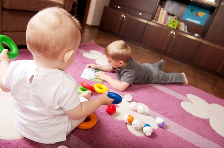 A boy aged 3 and a girl aged 1 are playing on the floor photo
