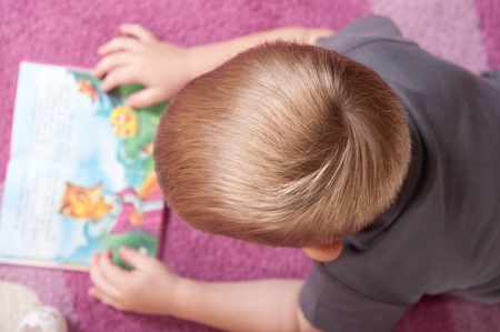 above head: Cute boy aged 3 is lying on the flor and reading book. View from above. Stock Photo