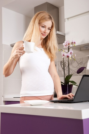 Young pregnant blonde woman drinking tea in kitchen and surfing the Internet photo
