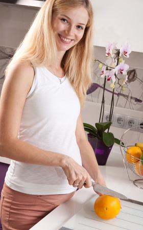 pregnant blonde: Young pregnant blonde woman cutting orange in kitchen