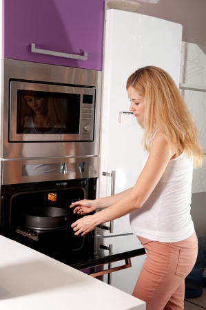Young pregnant blonde woman cooking in kitchen photo