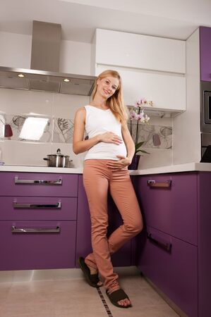 lady slipper: Young pregnant blonde woman in kitchen holding her belly