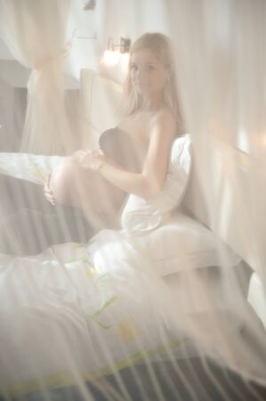 Attractive pregnant blonde resting in bed. Partly hidden by curtain. photo