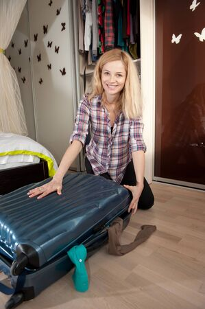 packing suitcase: Young blonde girl packing her travel bag Stock Photo