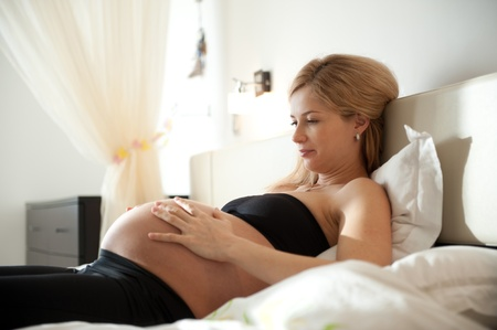 Young pregnant blonde lying in bedroom and holding her belly