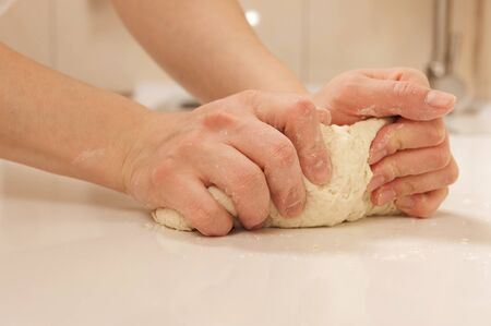 Female cook kneading dough in her kitchen photo