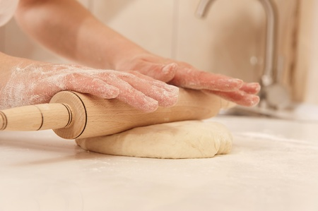 biscuit dough: Female cook rolling dough with rolling-pin. Closeup view
