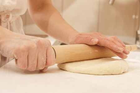 rollingpin: Female cook rolling dough with rolling-pin. Closeup view