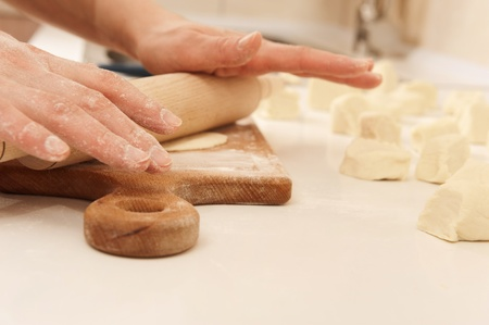 Female cook rolling dough with rolling-pin. Closeup view photo